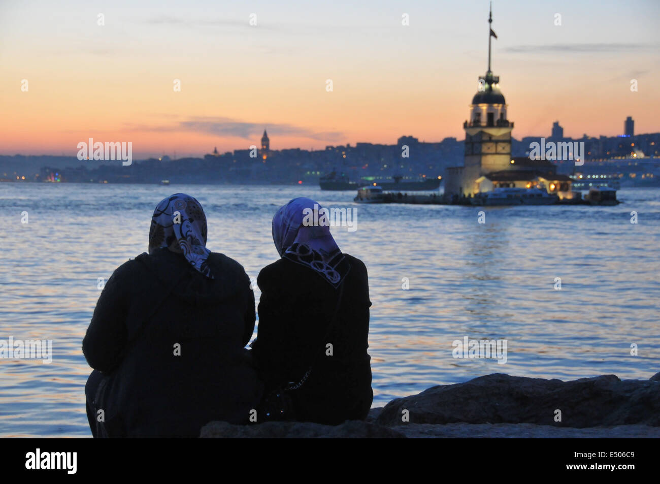 Dos mujeres relajarse en la Üsküdar waterfront al atardecer. Torre de la doncella (K?z Kulesi) puede verse Imagen De Stock