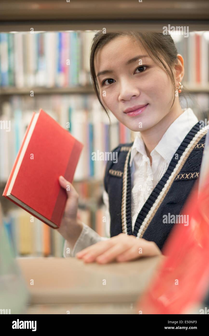 Chica sacando un libro rojo Imagen De Stock