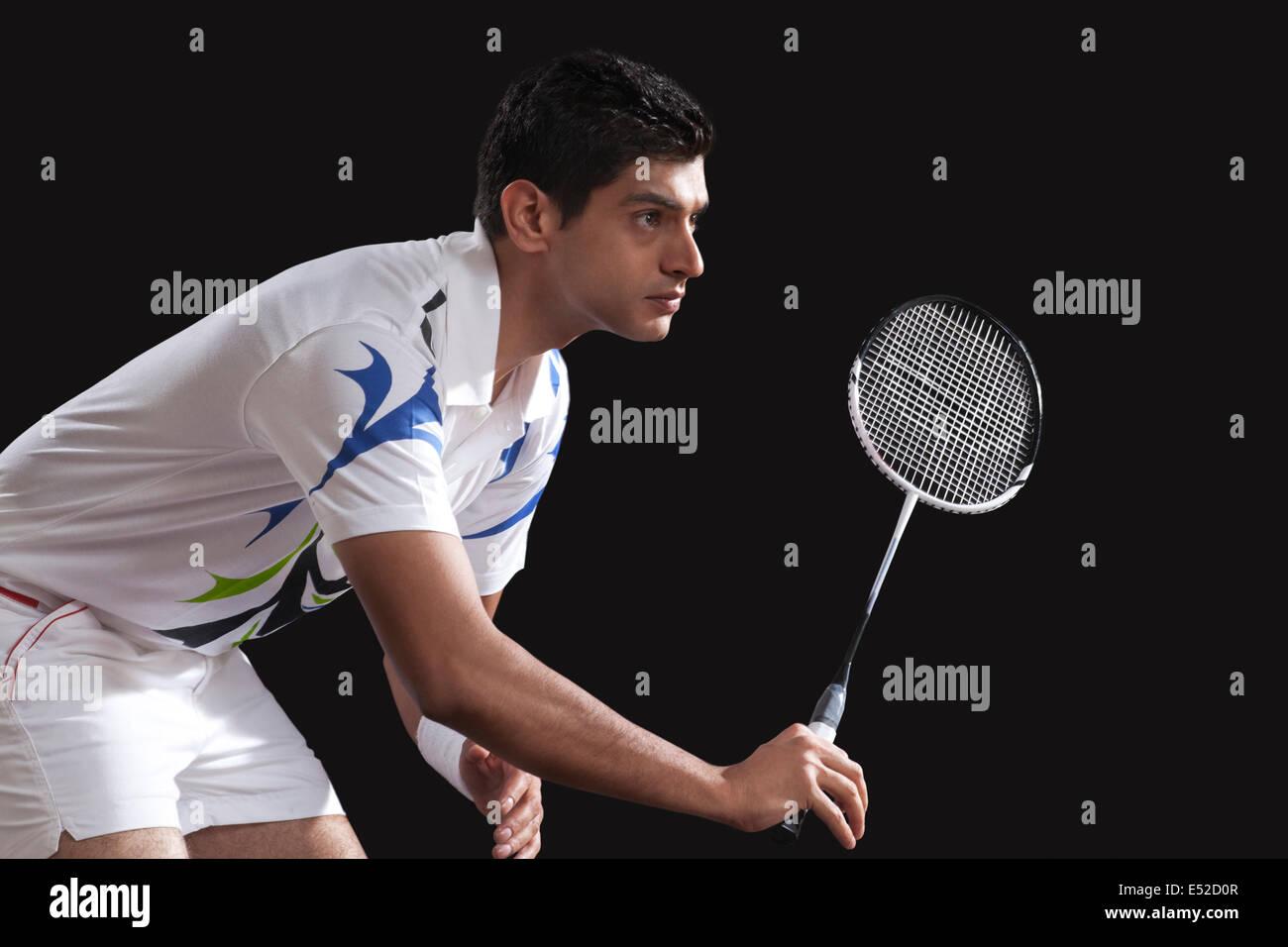 Macho joven jugador con raqueta jugar bádminton aislado sobre fondo negro Imagen De Stock