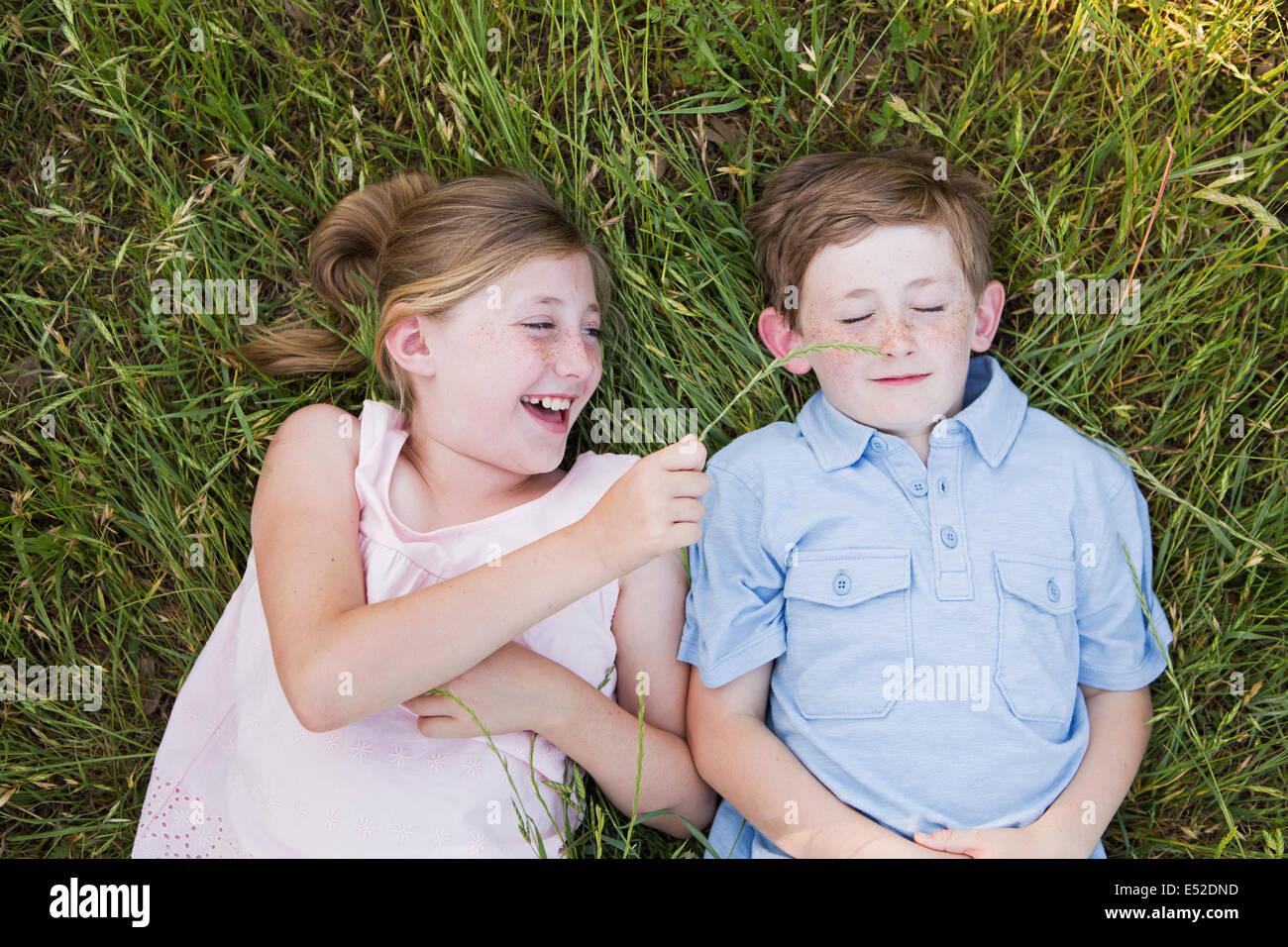 Dos niños, hermano y hermana acostada de lado a lado sobre la hierba Imagen De Stock