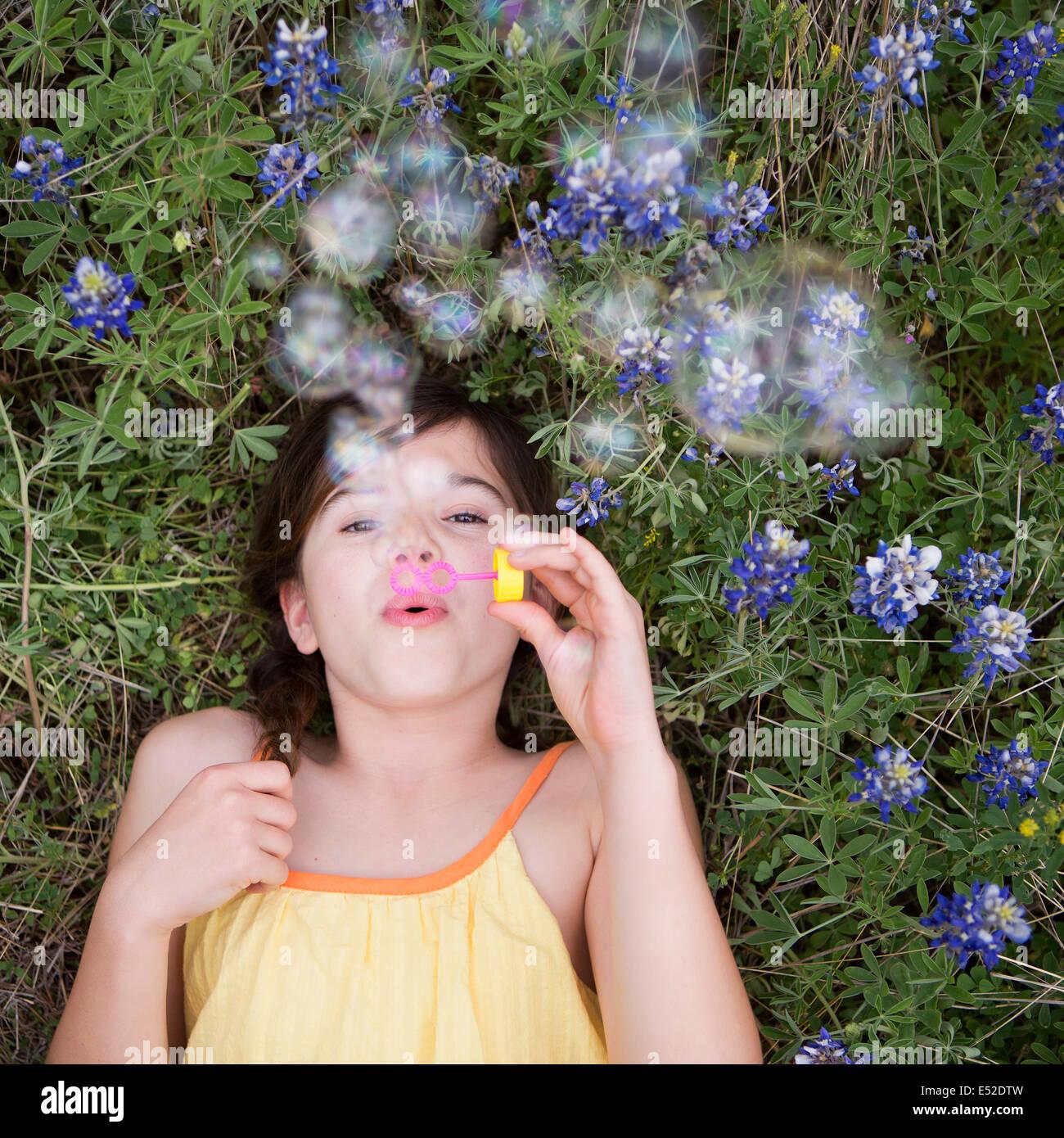 Una chica acostada soplando burbujas en el aire. Imagen De Stock