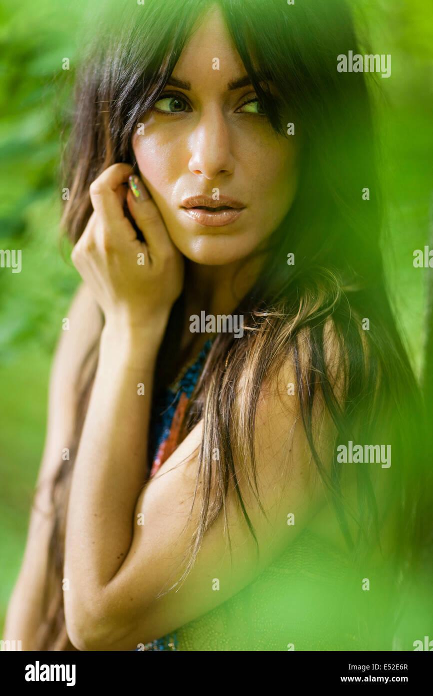 Una mujer con el cabello marrón largo al aire libre en los bosques. Imagen De Stock