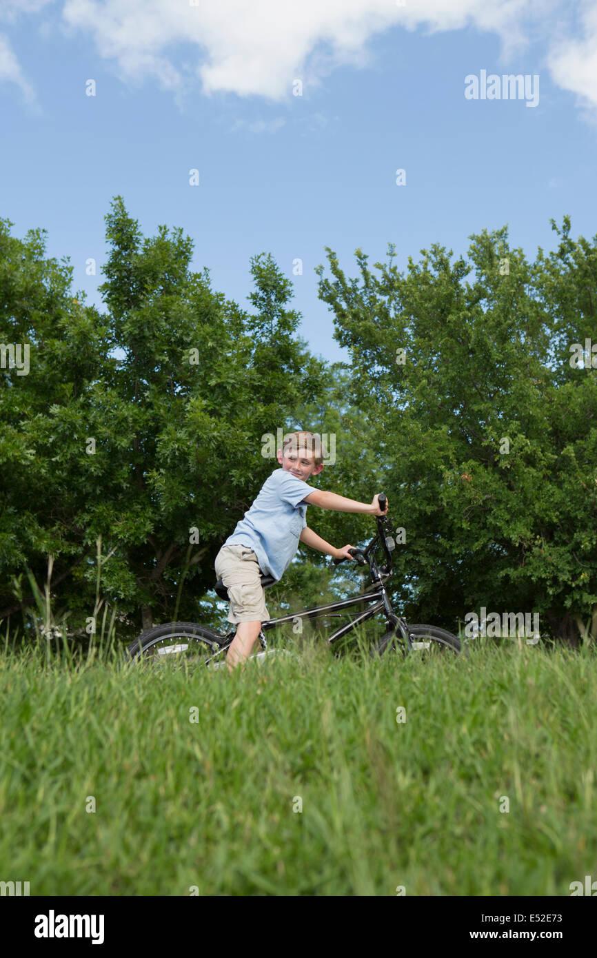 Un muchacho en bicicleta a través de la hierba en una pradera. Foto de stock