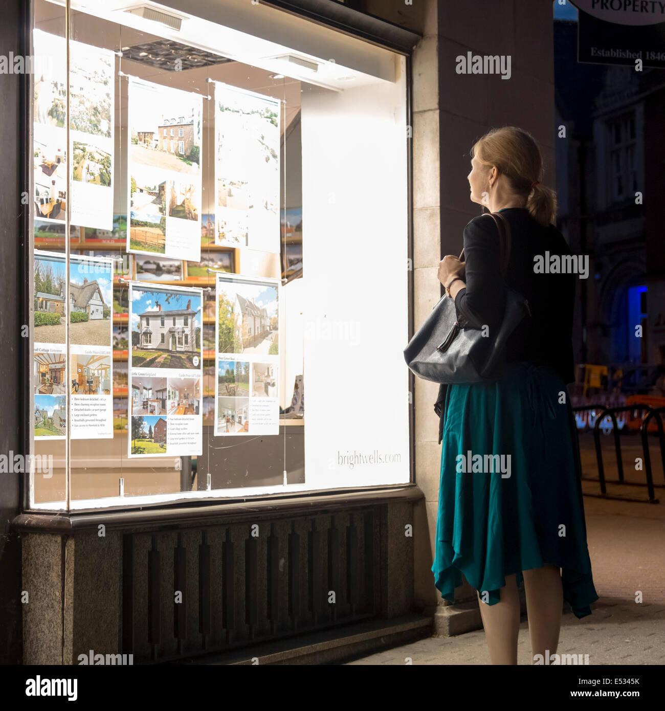 Mujer mirando por una ventana de agentes de la propiedad inmobiliaria en la noche, Reino Unido. Imagen De Stock