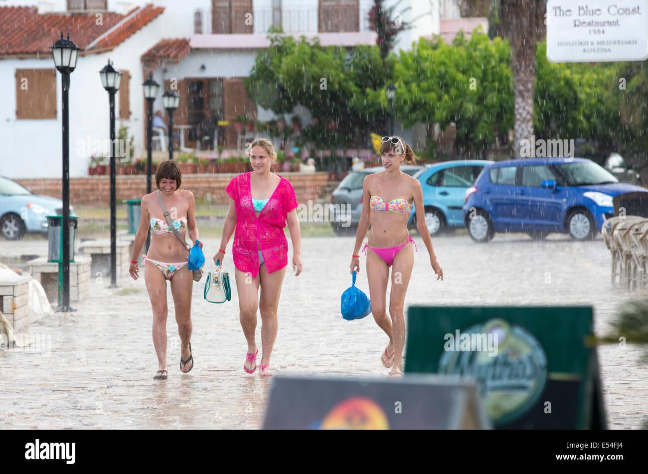 Las mujeres jóvenes en las lluvias y granizo de una tormenta en Sivota, Grecia. Imagen De Stock