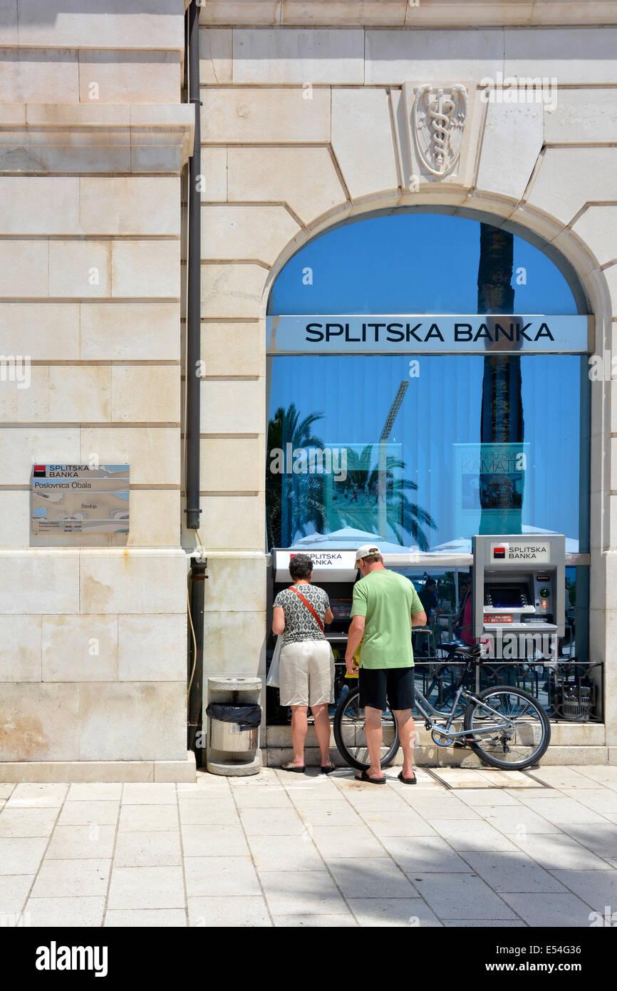Par de pie por un cajero automático fuera de una sucursal de la Splitska Banka (propiedad de Société Générale) en el centro de la ciudad de Split Foto de stock