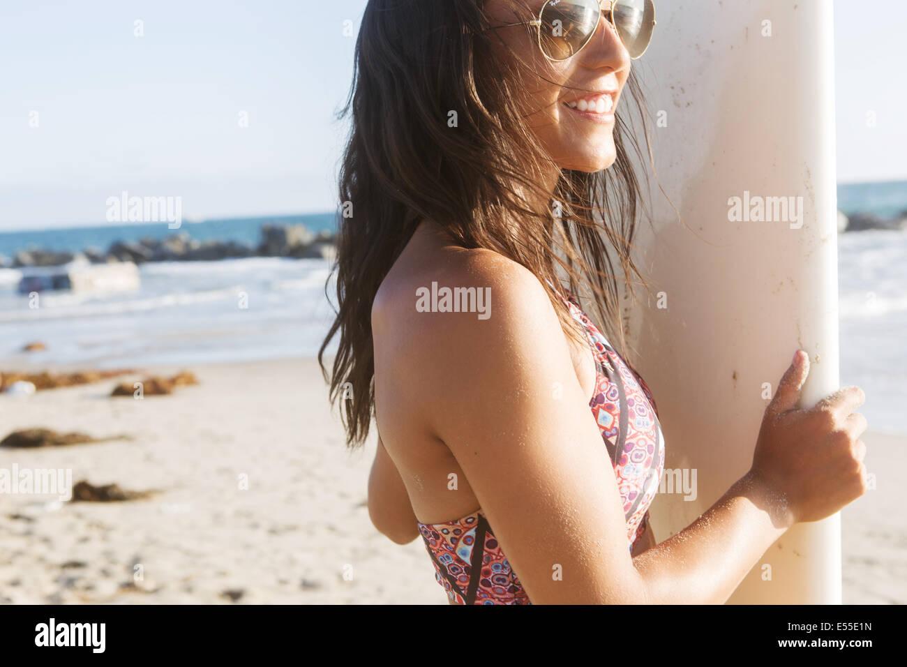 Mujer joven surfista con gafas de sol sonriente mientras mantiene las tablas de surf en la playa. Imagen De Stock