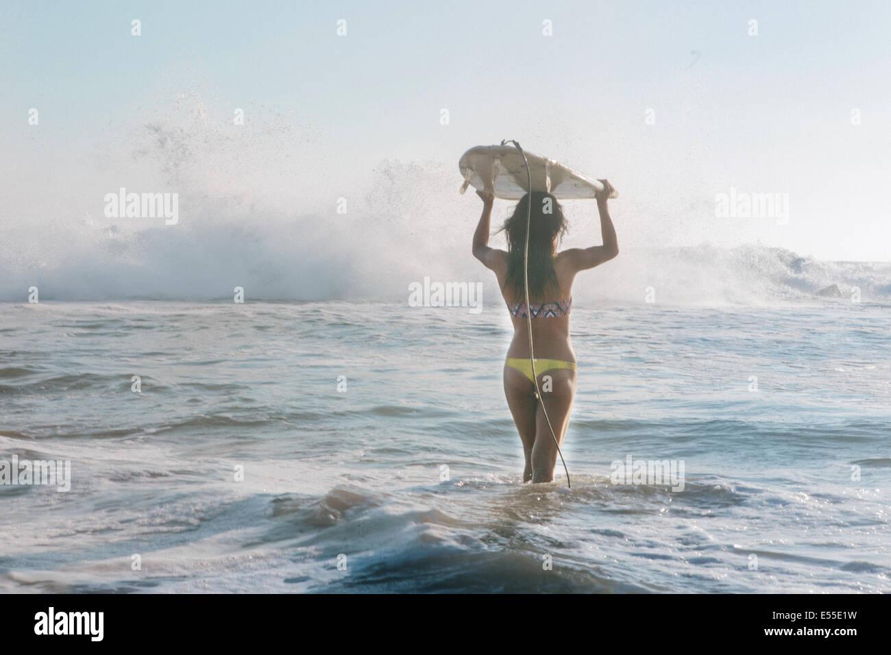Mujer joven surfista llevar tablas de surf en la cabeza caminando hacia el romper de las olas Imagen De Stock