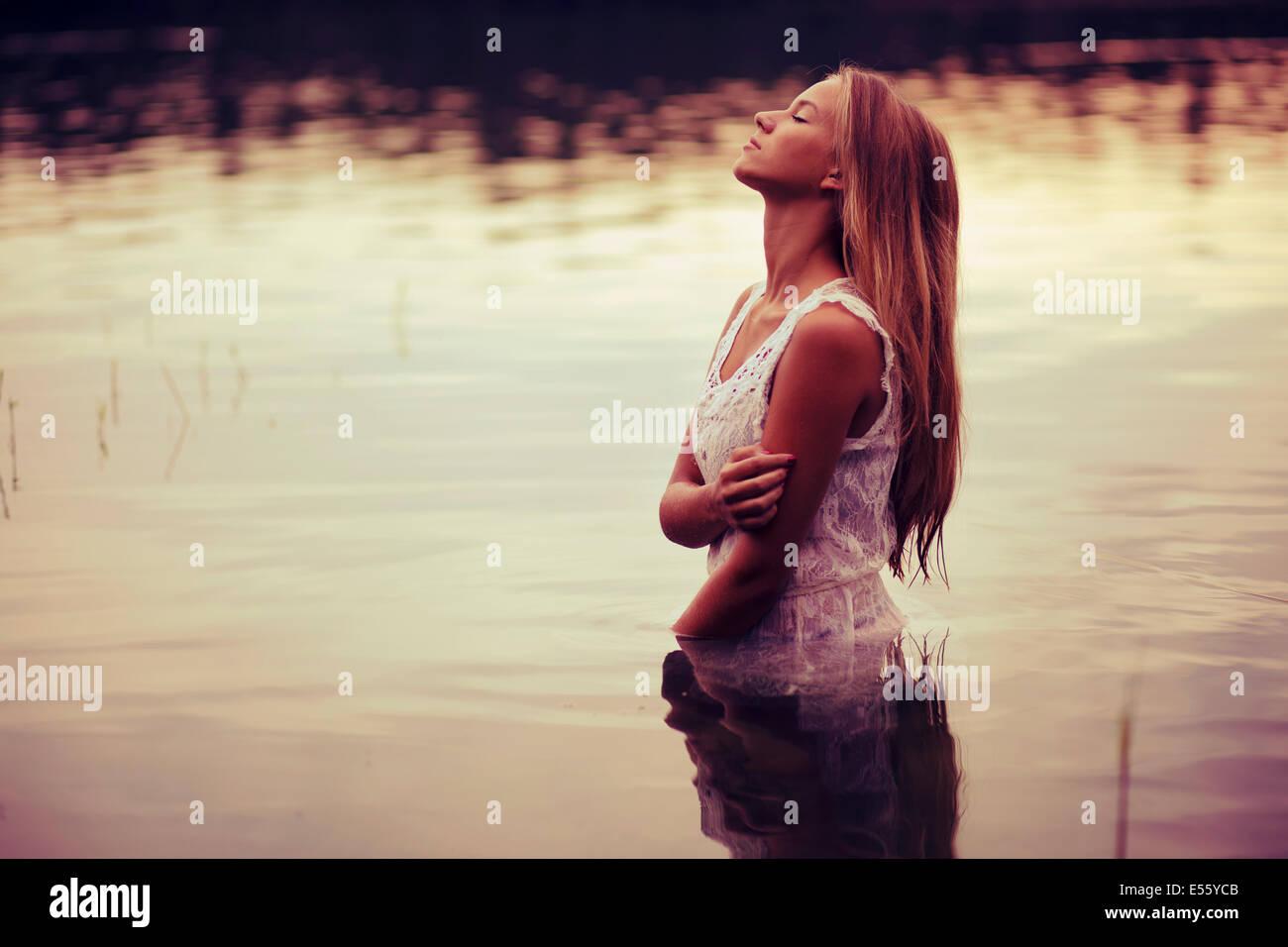 Mujer joven en vestido blanco parado en agua Imagen De Stock