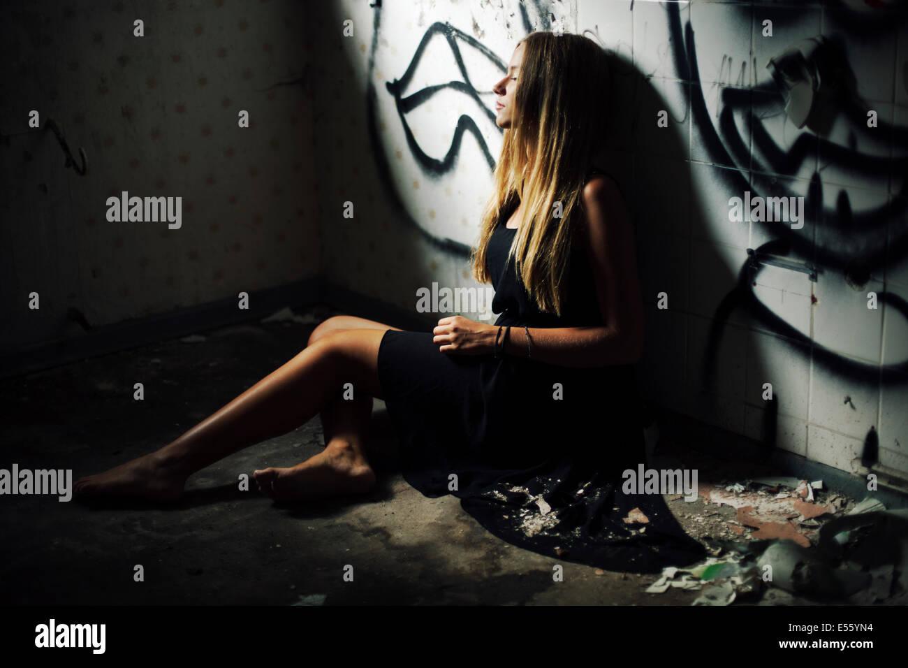 Mujer joven sentada en el suelo sucio Imagen De Stock