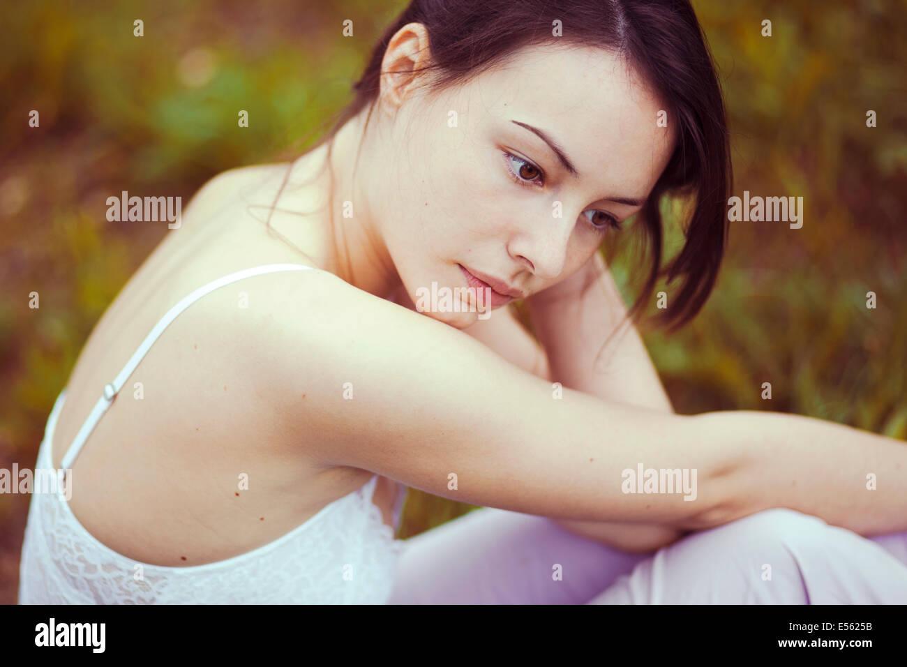 Pensativo joven mujer sentada sobre una pradera Imagen De Stock
