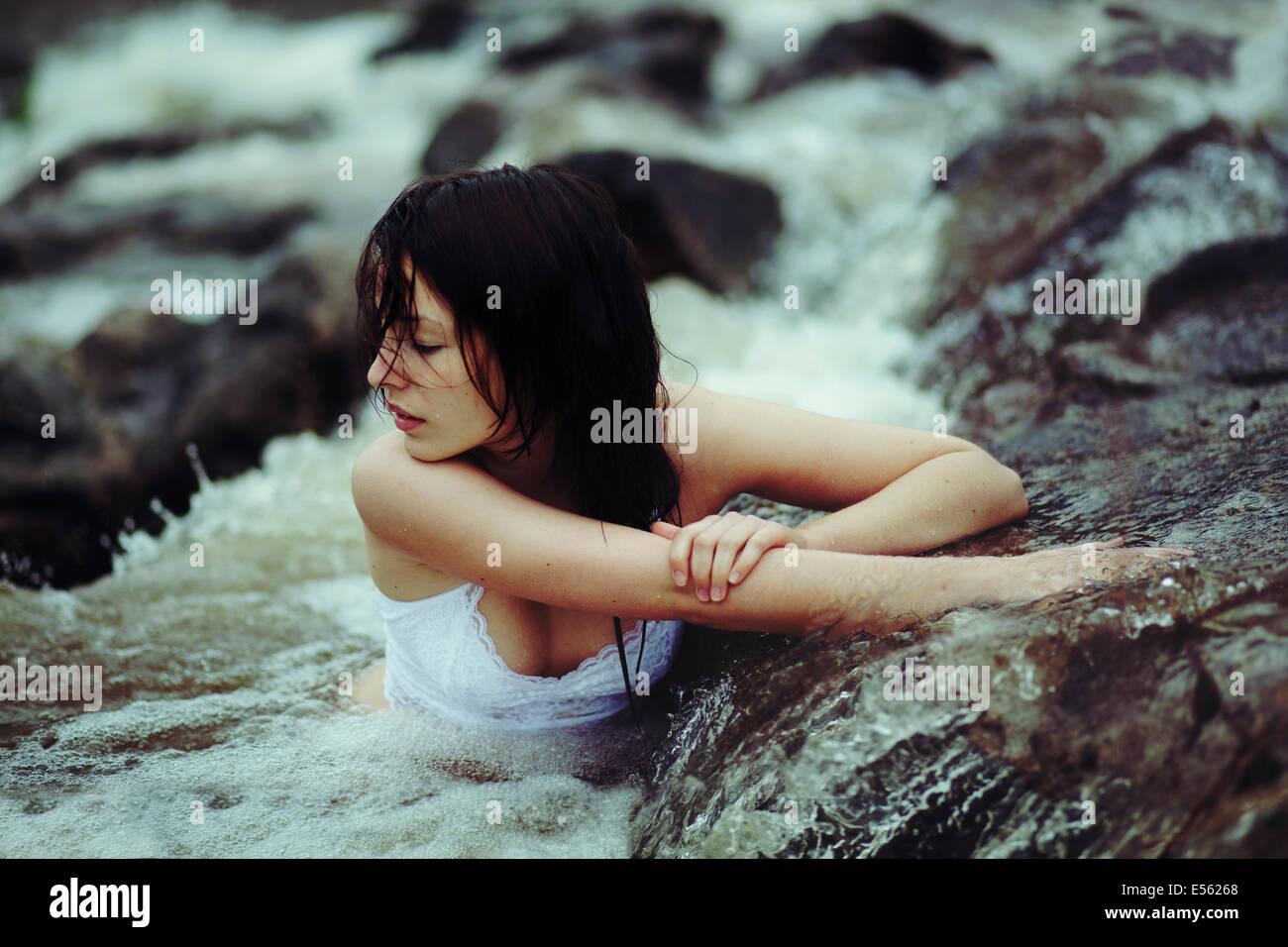 Mujer joven está sentado en un arroyo Imagen De Stock
