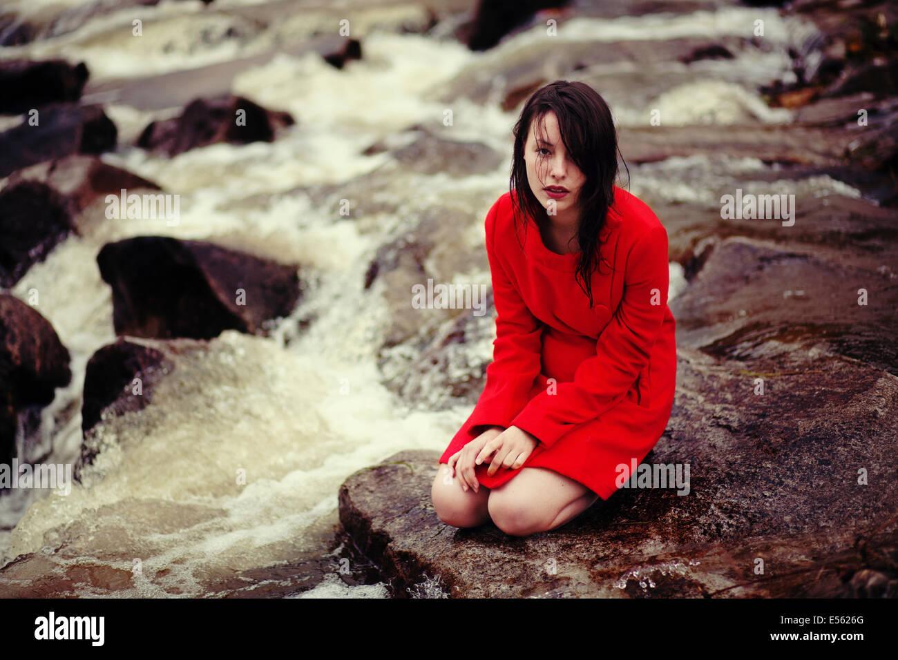 Mujer joven está sentado sobre un arroyo Imagen De Stock