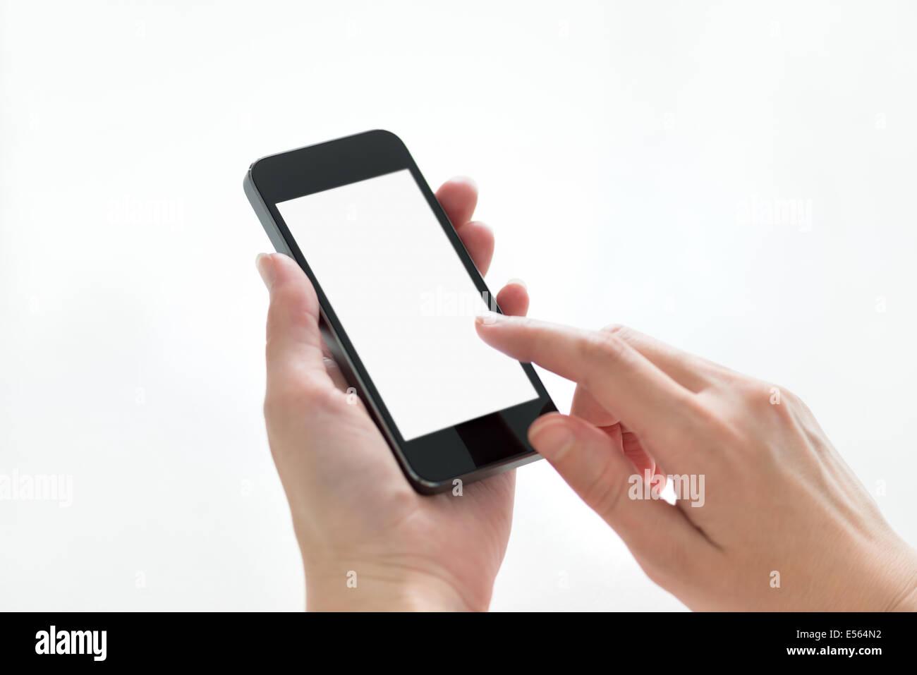 Manos femeninas y conmovedora celebración en mobile smartphone con pantalla en blanco. Aislado sobre fondo Imagen De Stock