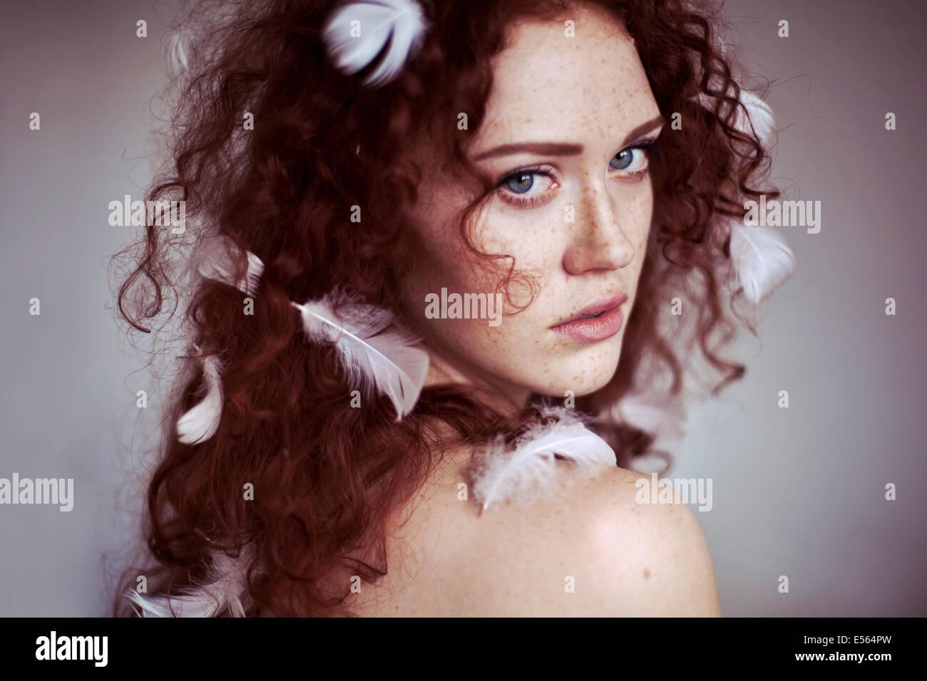 Mujer joven con plumas en su cabello Imagen De Stock