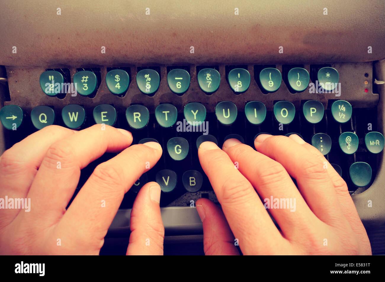 Primer plano de las manos de un hombre escribiendo en una vieja máquina Foto de stock