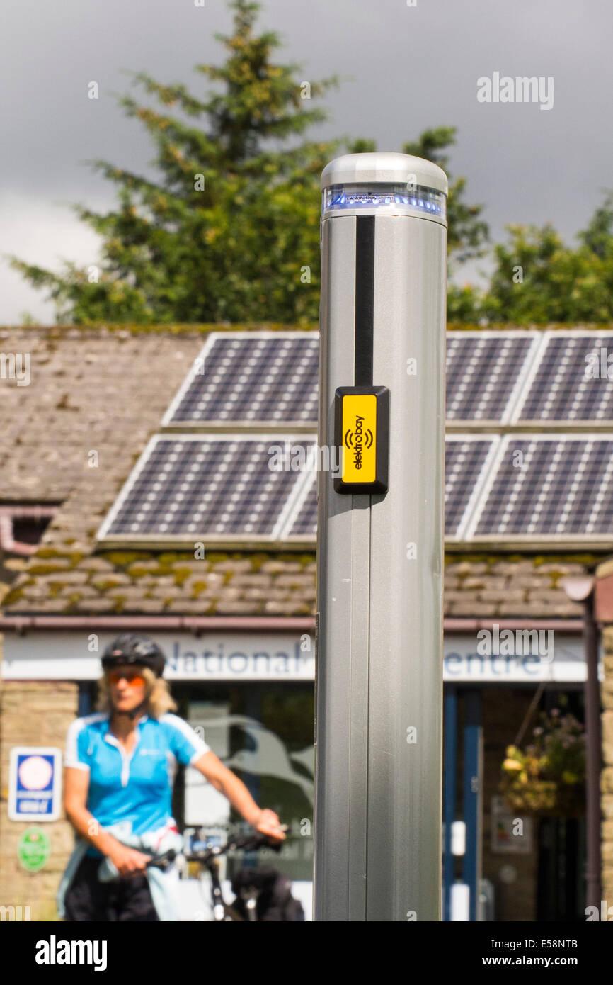 Una estación de recarga de vehículos eléctricos están cargadas por paneles solares en el Centro Imagen De Stock