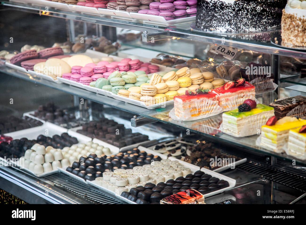 Una Pastelería tienda mostrar con una selección de pasteles, chocolates y macarons en Chorlitejo Town, Imagen De Stock