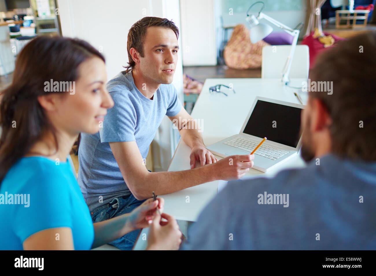 Joven escuchando a su socio de negocios en una reunión celebrada en la oficina Imagen De Stock