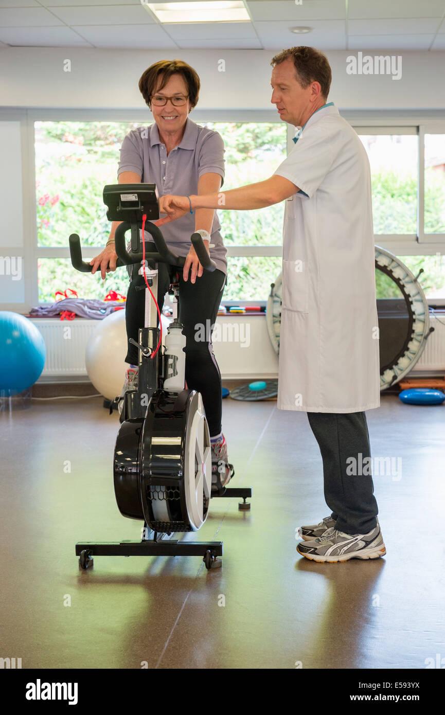 Fisioterapeuta ayudar a un paciente a montar una bicicleta de ejercicio Imagen De Stock