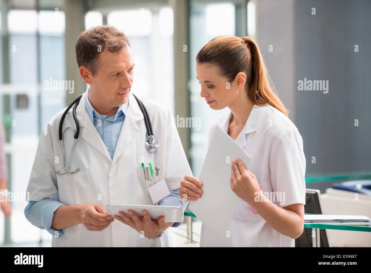 Dos médicos analizando un informe médico sobre la tableta digital en el hospital Foto de stock