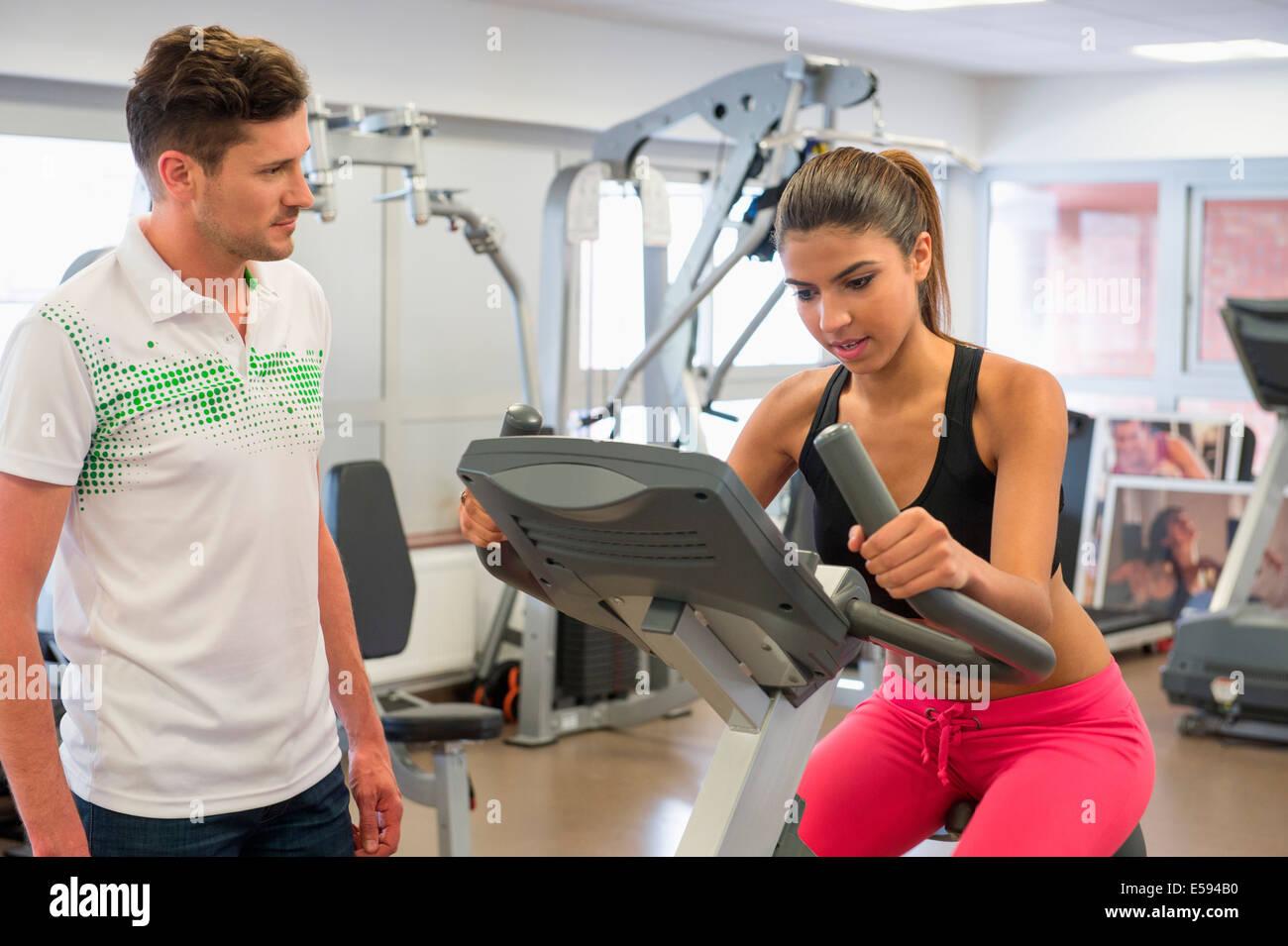 Instructor de una mujer en clase de spinning en el gimnasio Foto de stock