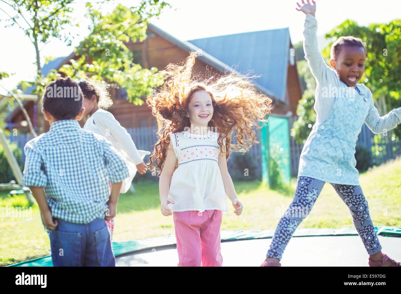 Los niños saltando en el trampolín al aire libre Foto de stock