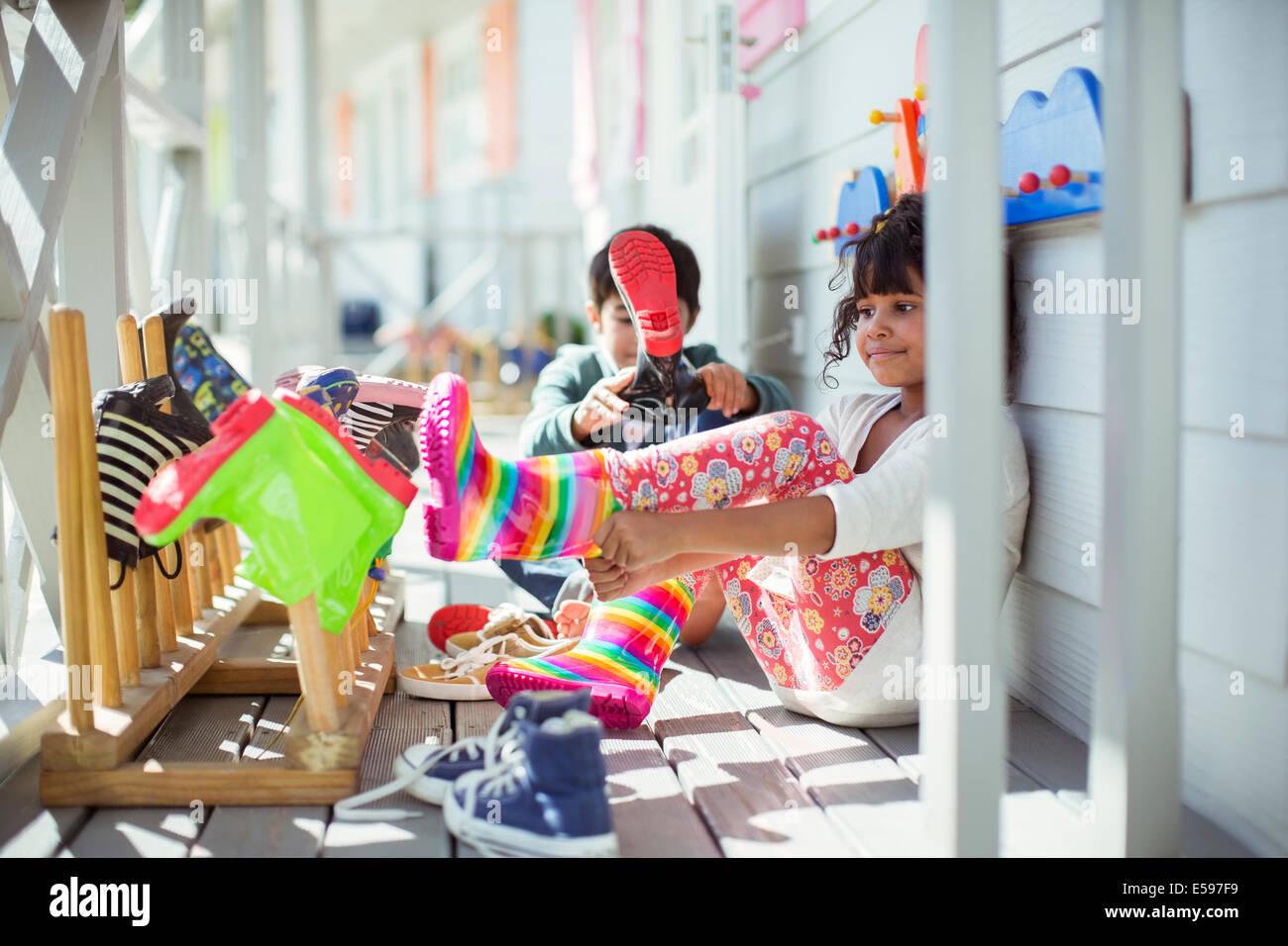 Los niños tirando de rainboots en porche Imagen De Stock