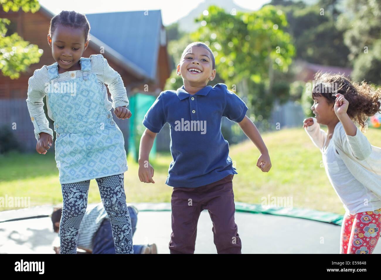Los niños saltando en el trampolín al aire libre Imagen De Stock