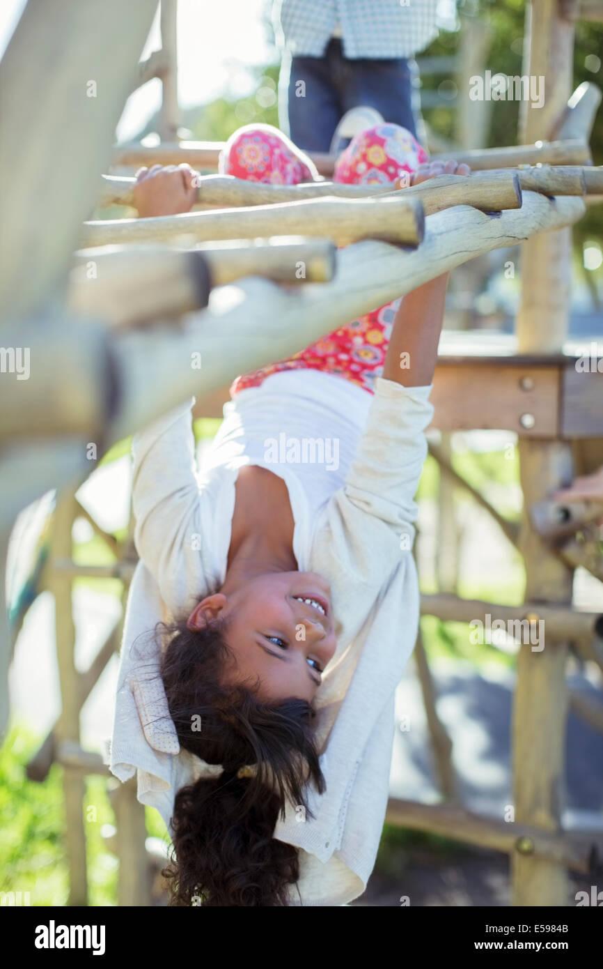 Chica escalada en monkey barras en playground Imagen De Stock