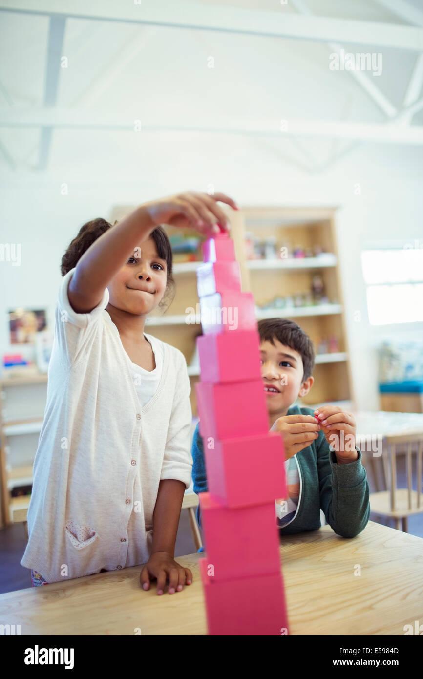 Los estudiantes apilar bloques en el aula Imagen De Stock