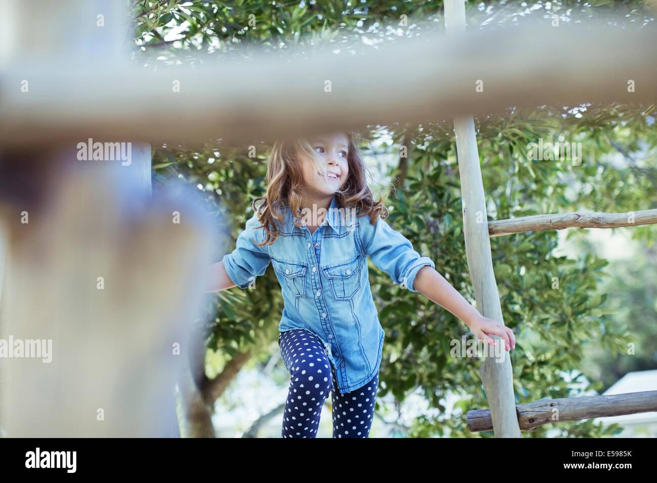 Chica escalada en estructura de juego Foto de stock