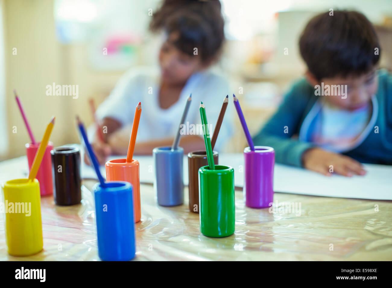 Lápices de colores sobre el escritorio en el aula Foto de stock