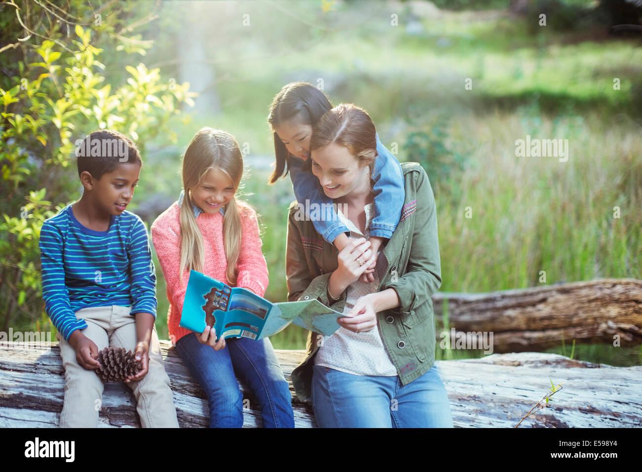 Los alumnos y el profesor leer mapa en el bosque Imagen De Stock