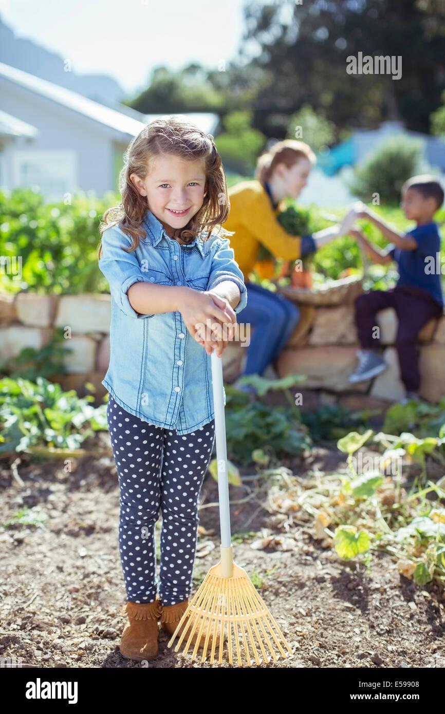 Chica sujetando el rastrillo en el jardín Imagen De Stock