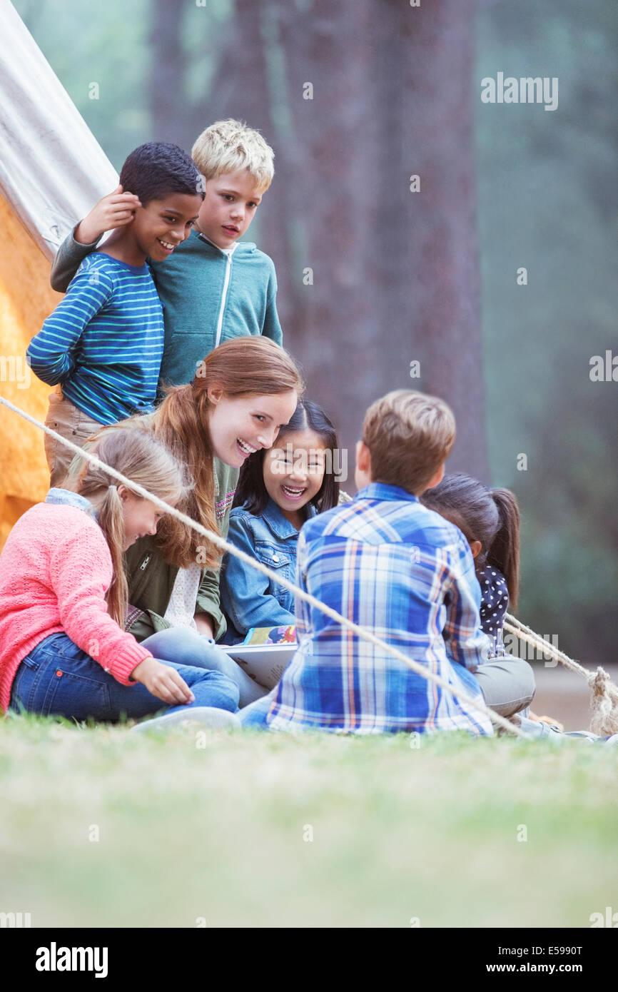 Los alumnos y el profesor lectura en camping Imagen De Stock