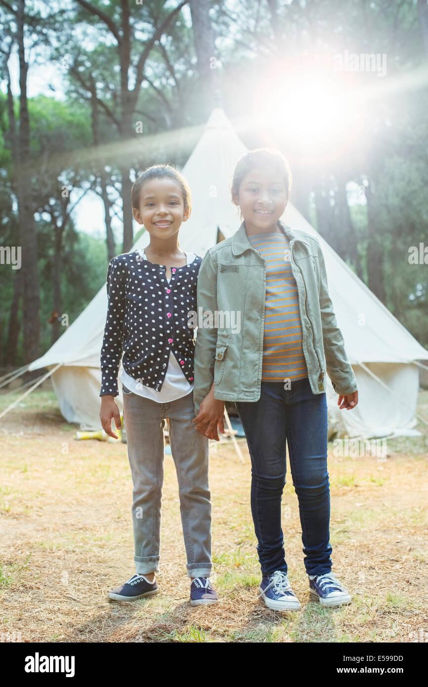 Chicas sonrientes por tienda en el camping Imagen De Stock