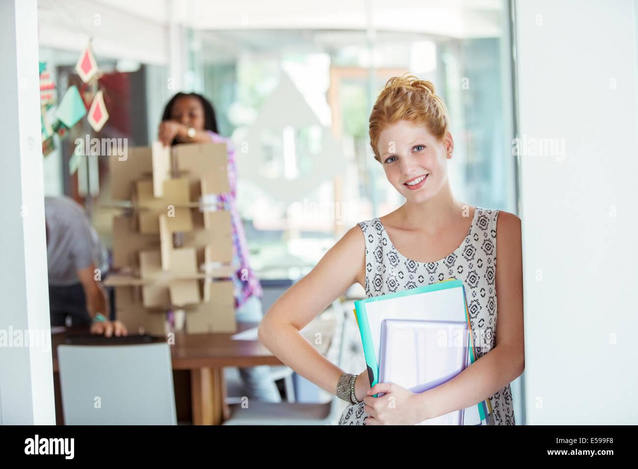 La empresaria llevando aglutinantes en Office Imagen De Stock