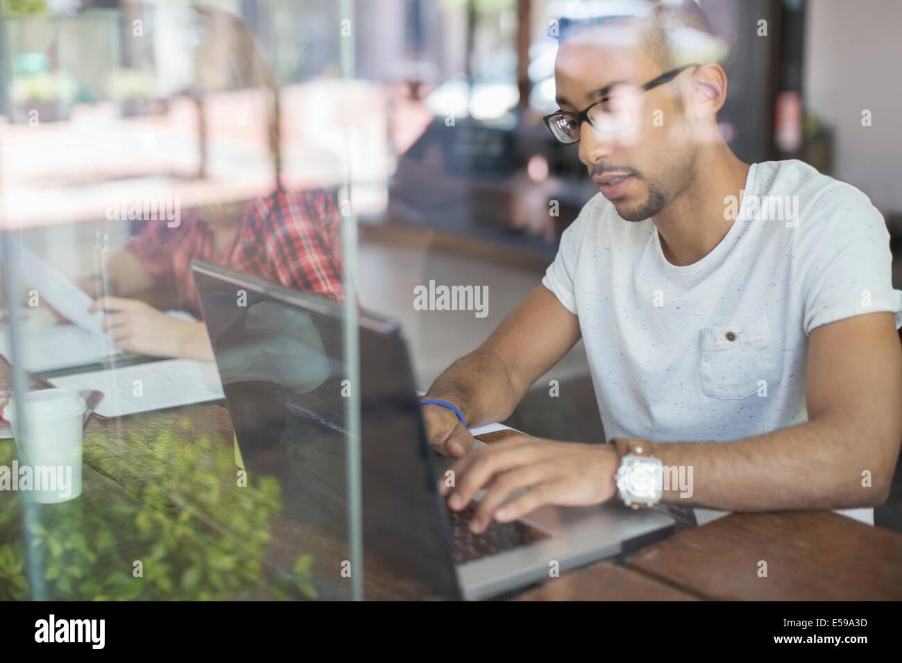 Hombre utilizando el portátil en la cafetería Imagen De Stock