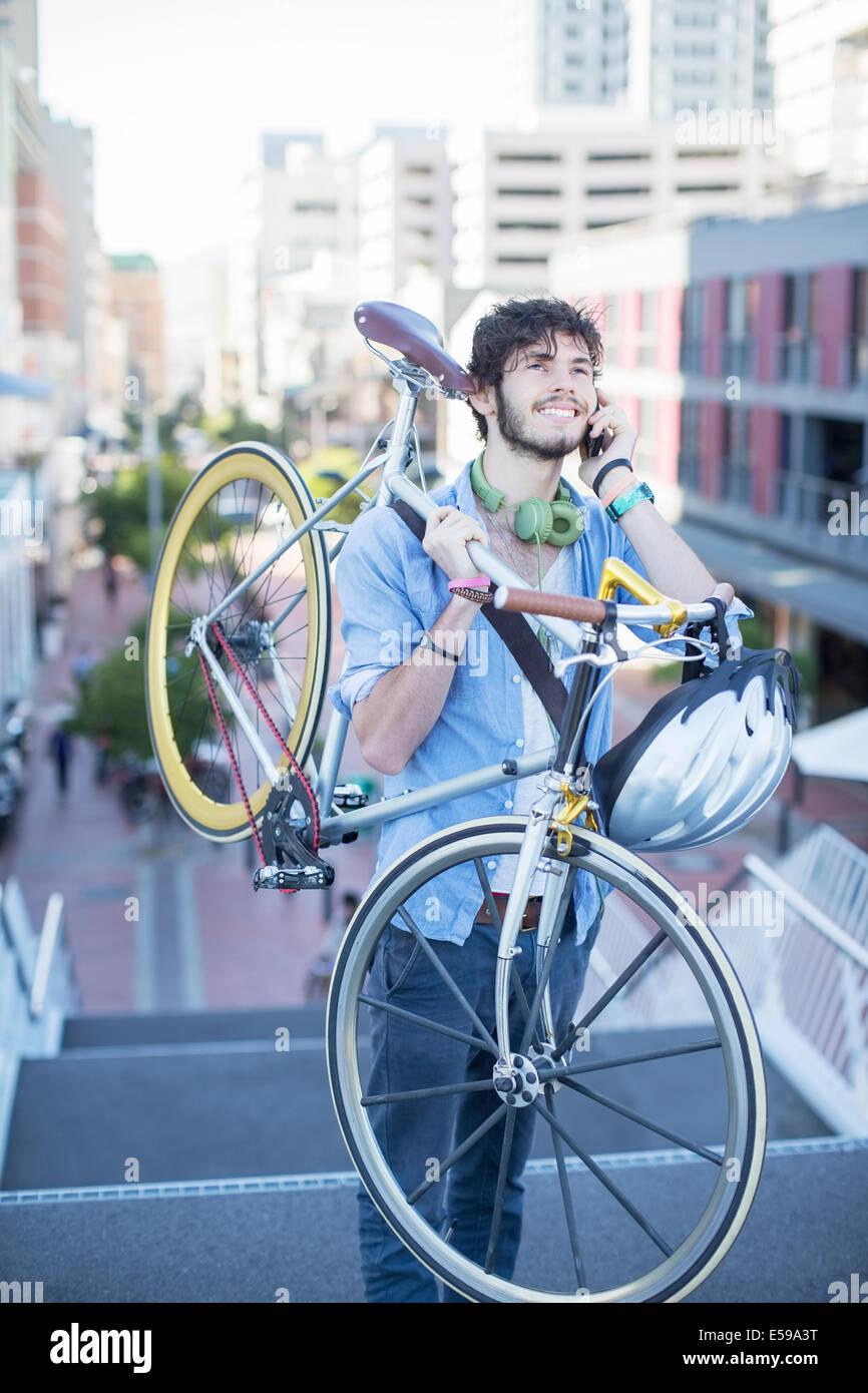 El hombre lleva la bicicleta en la ciudad pasos Foto de stock