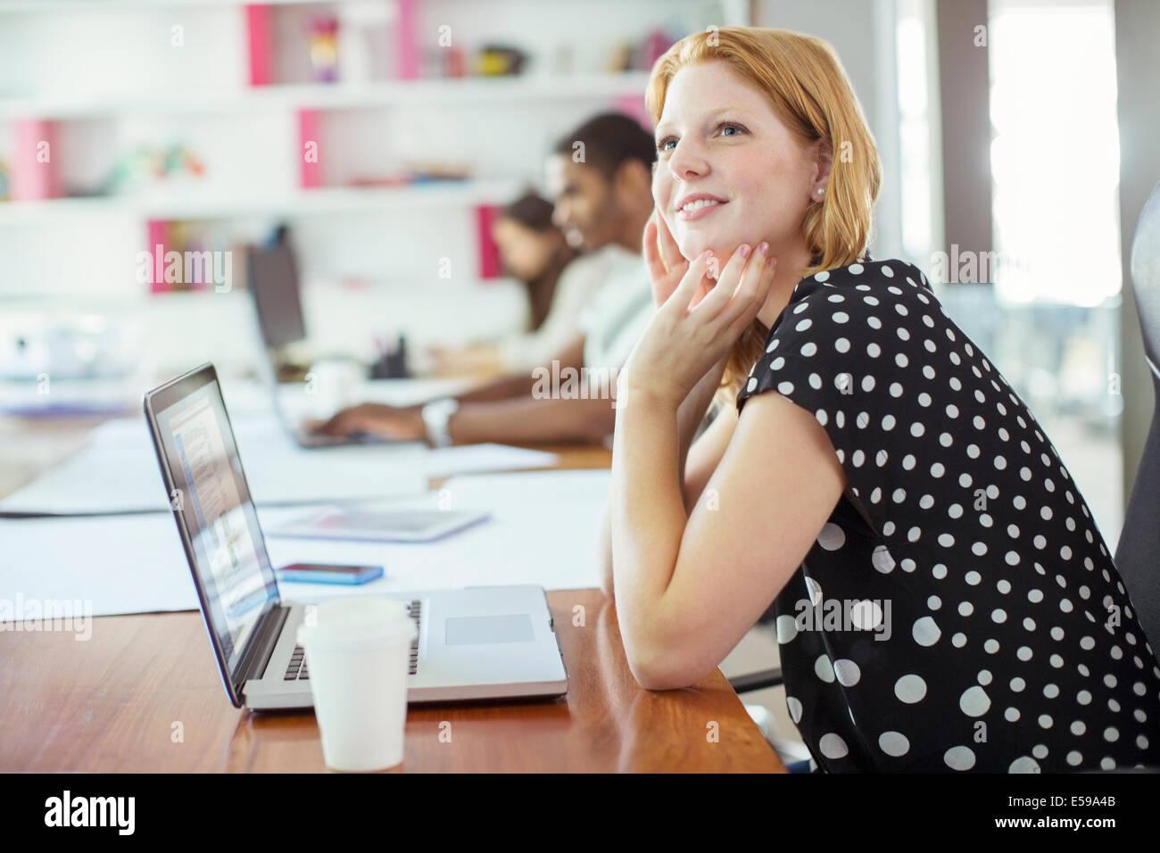 Mujer trabajando en una mesa de conferencias en la oficina Foto de stock