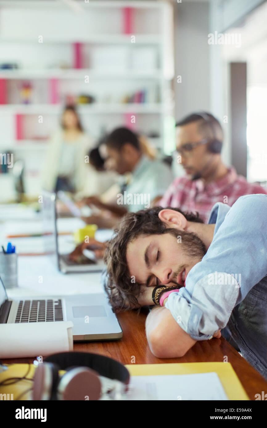 Hombre dormido en un escritorio en la oficina Foto de stock