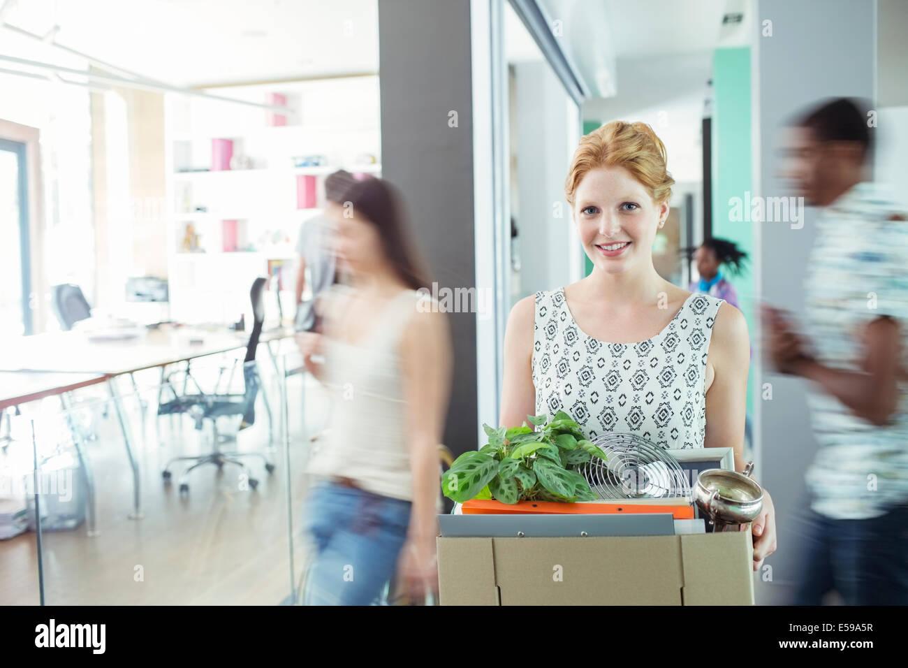 Mujer que llevaba la caja de cartón en la oficina Foto de stock