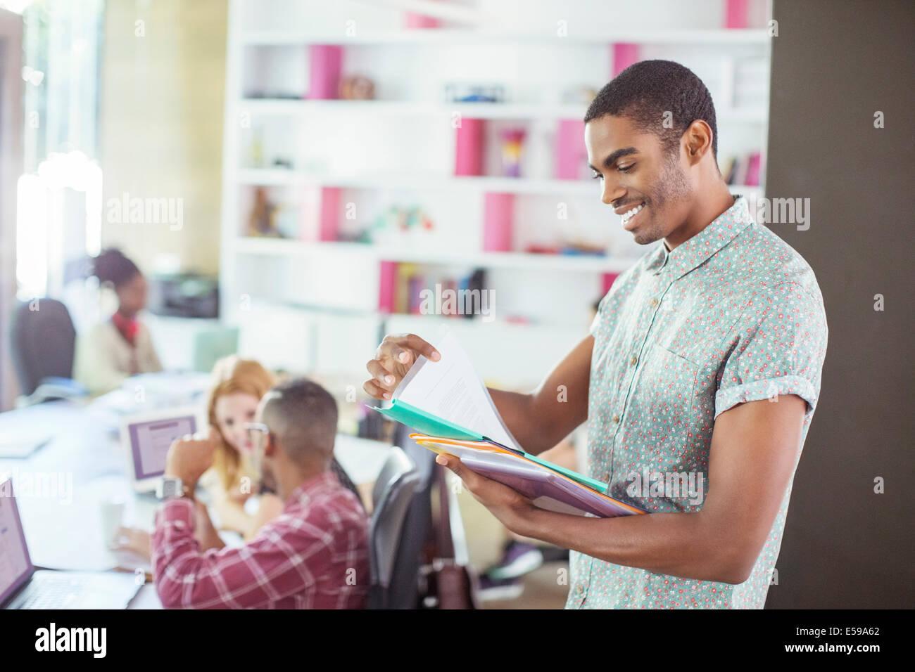 Hombre leyendo las carpetas de oficina Imagen De Stock