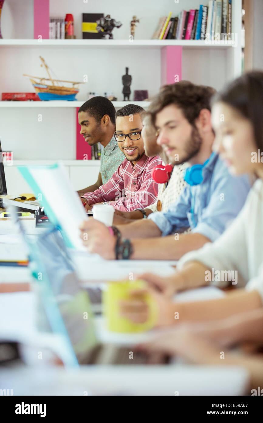 Las personas que trabajan en la mesa de conferencias en la oficina Imagen De Stock