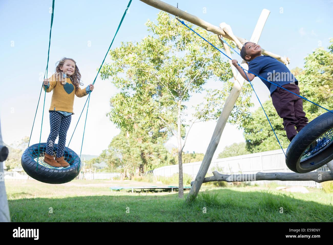 Niños jugando en columpios de neumático Foto de stock