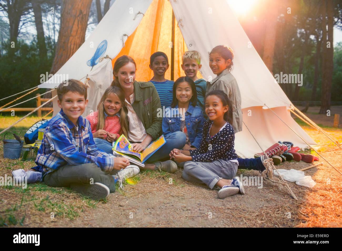 Los alumnos y el profesor sonriente en camping Imagen De Stock