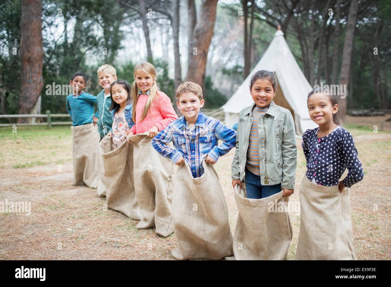 Los niños sonríen al inicio de la carrera de sacos Imagen De Stock