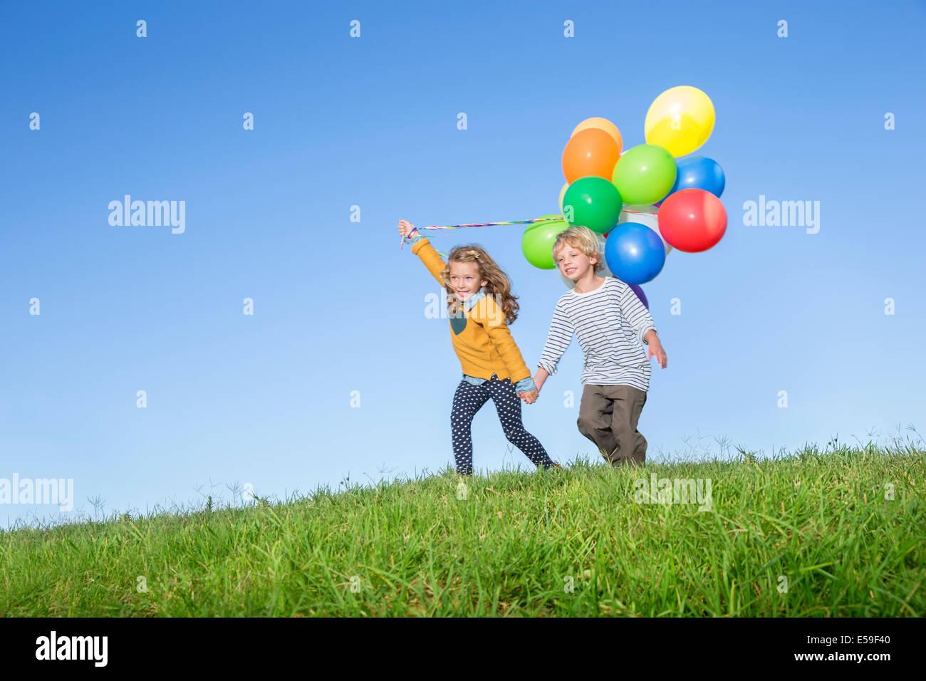 Los niños con montón de globos en grassy hill Imagen De Stock