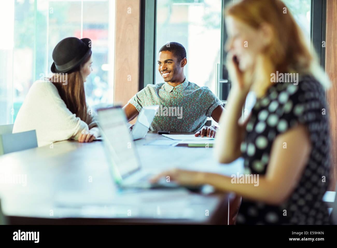 Las personas que trabajan en la mesa de conferencias en la oficina Foto de stock